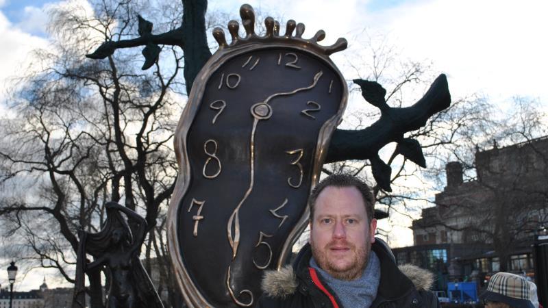 Mitt i bilden syns en bronsskulptur med en deformerad urtavla på ett dött träd. Nere till höger står en man i mörk jacka med pälskrage.