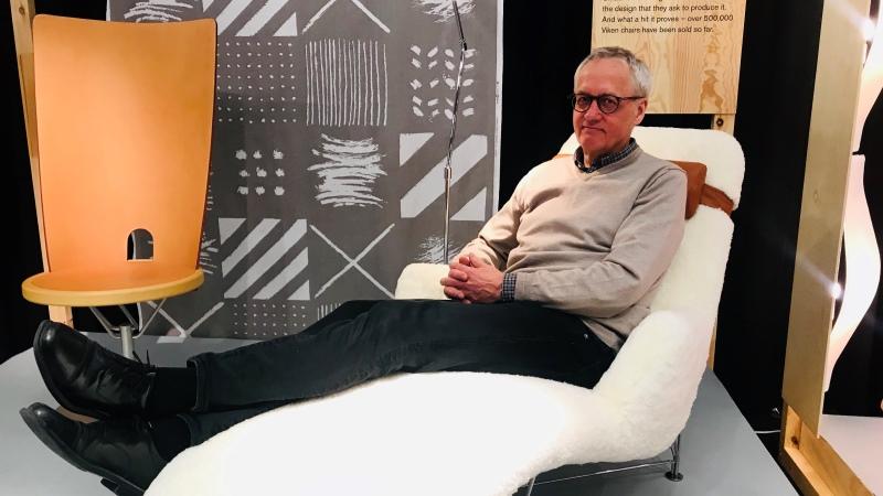 Man i grått och svart i designstol