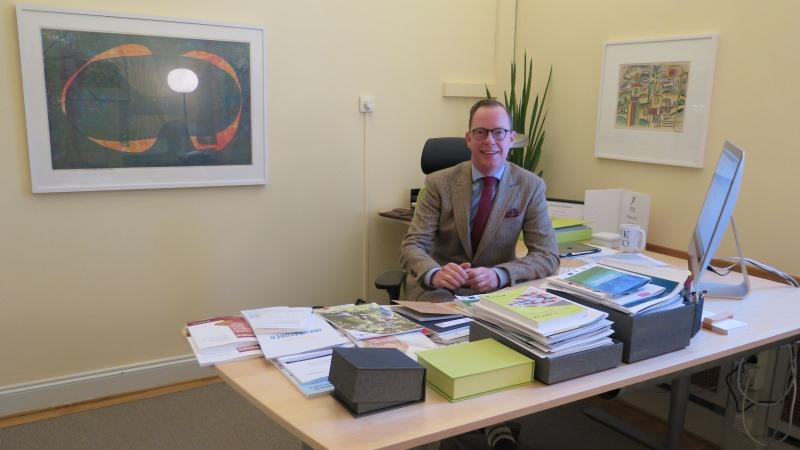 Kortklippt leende man i glasögon, kostym och slips sitter vid ett välfyllt med prydligt skrivbord.