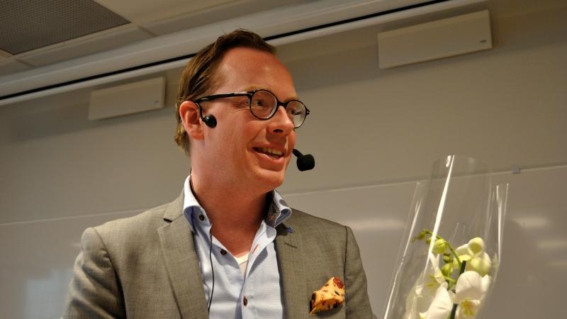 Landstingsråd Daniel Forslund. Han ler, har hörlurar med mikrofon på huvudet, bär glasögon, är klädd i skjorta och grågrön kavaj samt håller i en orkidée han fått som tack för sin insats.