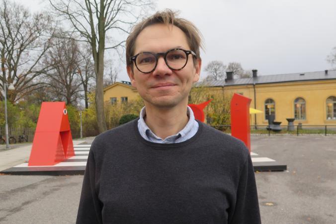 En man med mörkt hår och glasögon står utomhus. I bakgrunden två orangea skulpturer.