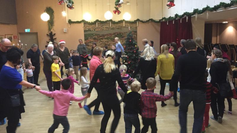 Barn och vuxna håller händer och dansar runt granen i dubbla ringar