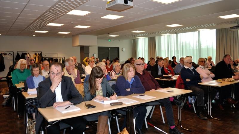 Deltagare vid konferensbord på rad i fullsatt sal under årsmötet.