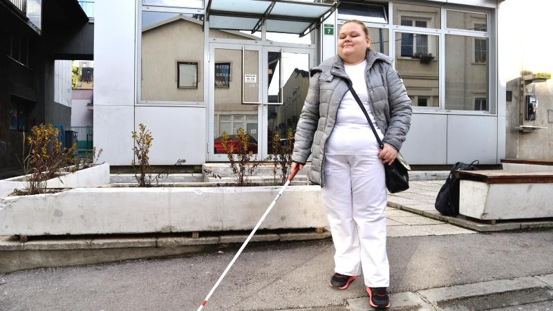 En ung småleende kvinna promenerar med vit käpp framför en byggnad i plåt och glas i Sarajevo.
