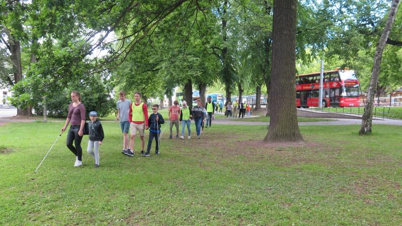 En grupp barn, ungdomar och vuxna kommer gående över en gräsmatta.
