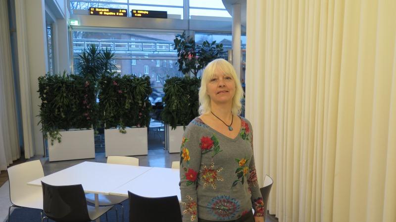 En blond kvinna med axellångt hår och lugg, klädd i blommig tröja. Hon står i en foajé där avgångskyltar till tunnelbanan hänger från taket i bakgrunden.