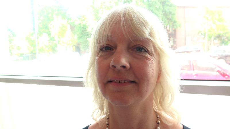 Närbild på en kvinna med luggklippt blont, kort hår som bär ett halsband med pärlor.