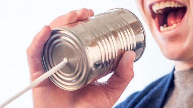 Ansikte i närbild, man pratar i en stålfärgad konservburk med tråd i botten, som en telefon.