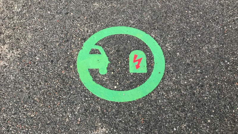 Symbol på asfalt i en parkeringsficka för laddning av elbilar. I en neongrön cirkel syns en halv bilkaross till vänster och en laddningstation med röd elblixt till höger.