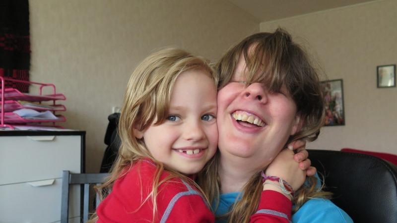 Kvinna och ung flicka omfamnar varandra och ler.