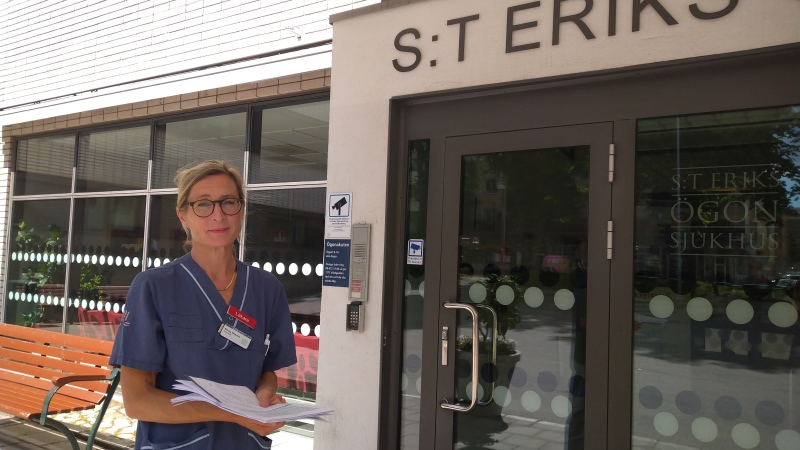 Blond kvinna med håret samlat i tofs, bruna glasögon och klädd i blå sjukhuskläder framför sjukhusets huvudingång.