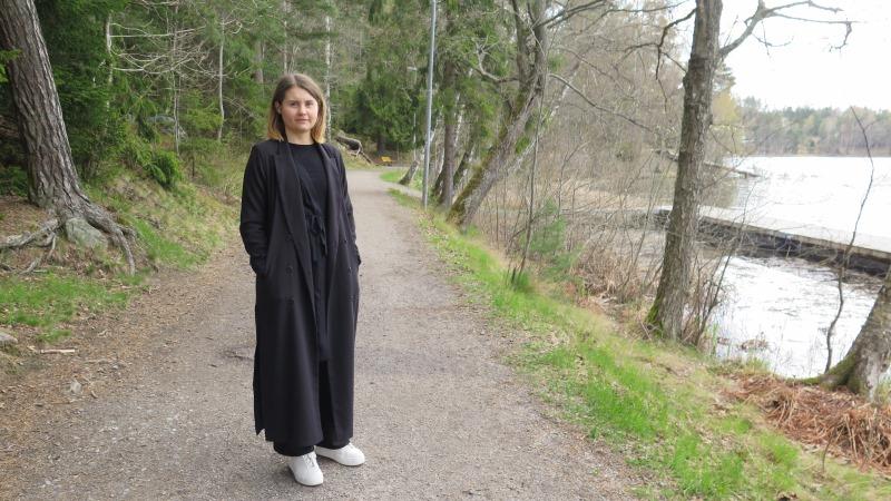 Emmatora Alfin har mörkblont axellångt hår och lång svart kappa. Hon står på en gångstig vid vattenbrynet.