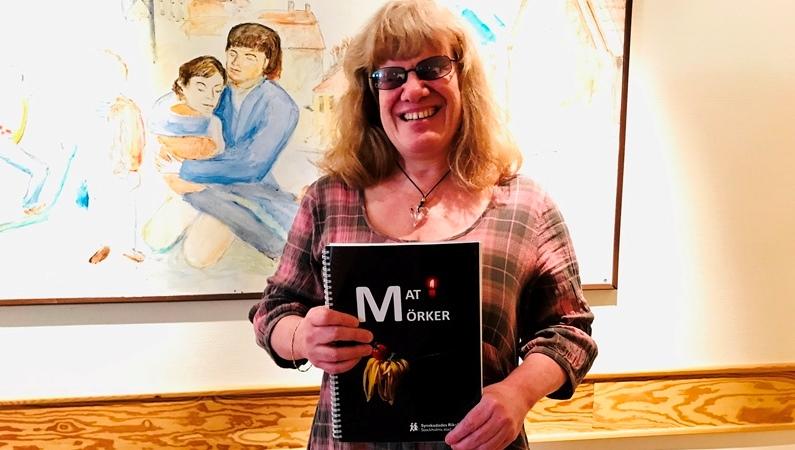 Leende kvinna med vågigt rågblont halvlångt hår med lugg, och glasögon. Håller i en bok som har ett svart omslag. Hon står framför en tavla med ett omfamnande par.