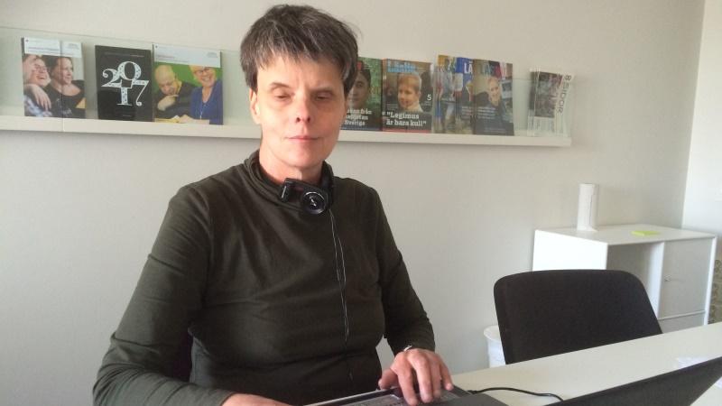 Eva Nilsson har mörkt, kort hår och brun polotröja. Hon sitter framför en laptop med hörlurar runt halsen.