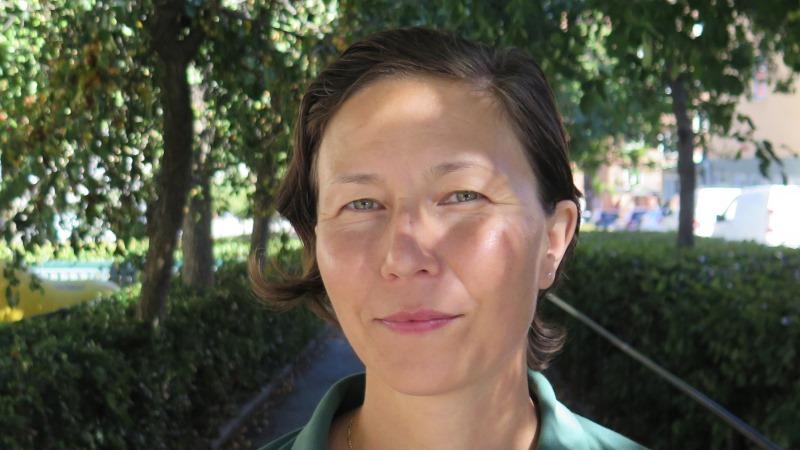 Närbild på en kvinna med kort, mörkt hår och gröna ögon i lummig parkmiljö.