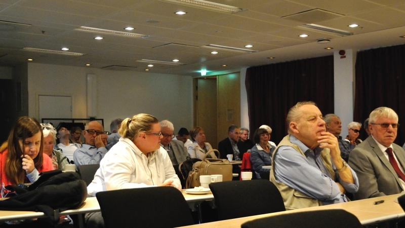 Lyssnande mötesdeltagare sitter på rad vid smala bord i ett konferensrum.