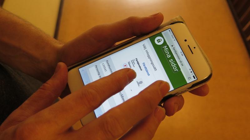 Händer som håller mobil med färdtjänstwebbsidan uppe