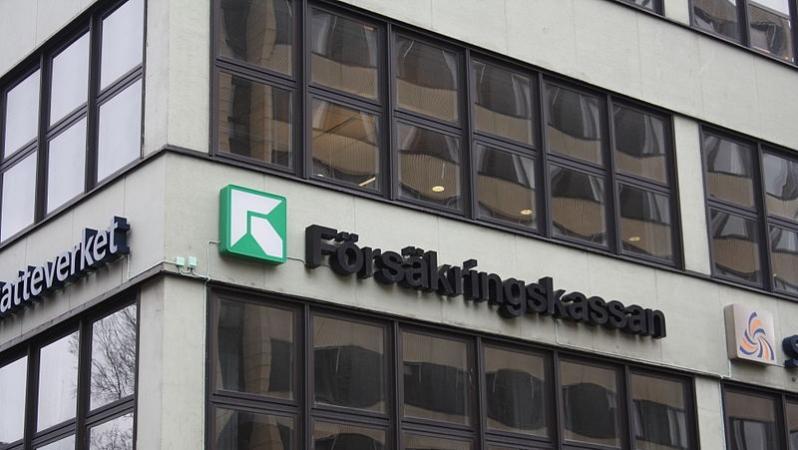 En grå husfasad med Försäkringskassans logotyp i grönt och vitt, samt namnet Försäkringskassan.