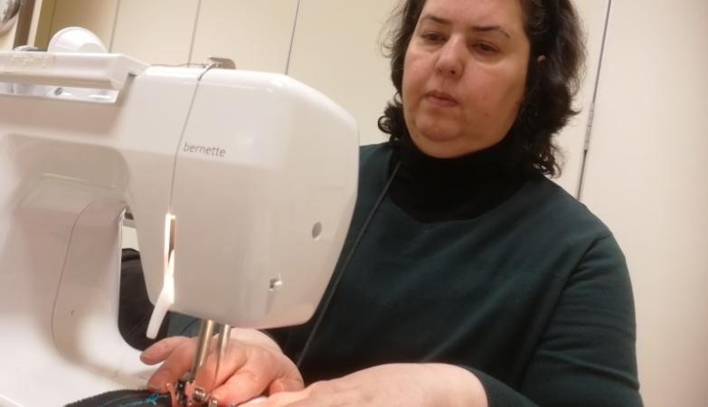 Kvinna med mörkt hår bakom symaskin.