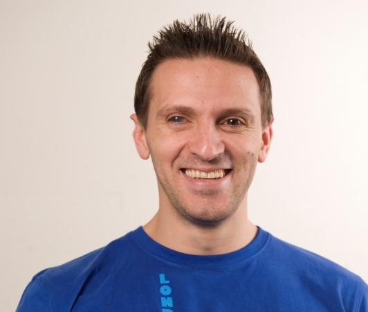 Fatmir Seremeti har kortklippt mörkbrunt hår och bruna ögon. Han ler brett och är klädd i en blå t-shirt.