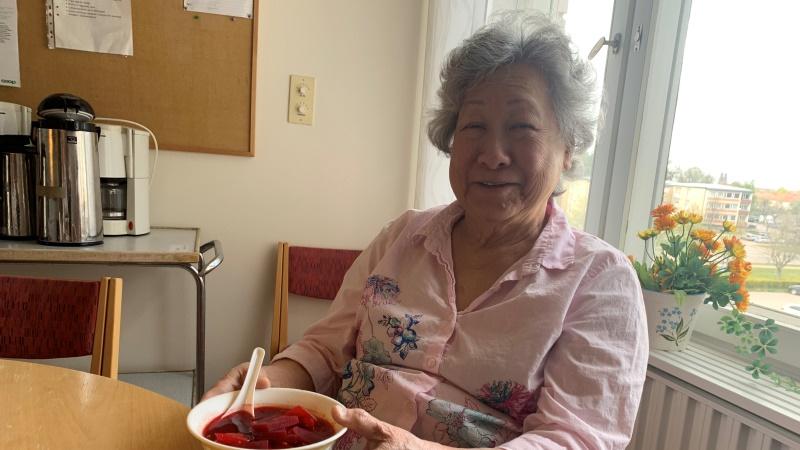 Leende kvinna med kort, grått vågigt hår, klädd i ljusrosa blus med blommönster, sitter vid ett köksfönster och håller i en vit djup tallrik med rödfärgat innehåll.