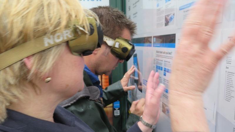 Två personer med glasögon med fingerad synoptik känner på en informationstavla i en busskur