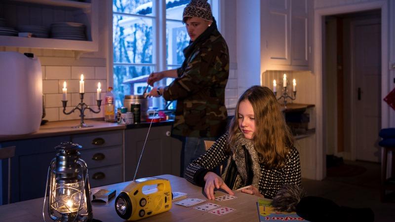 Interiör från ett kök utan el. En man i vinterkläder lagar mat på spritkök, en flicka spelar kort vid bordet. Flera ljusstakar brinner och på bordet står en fotogenlampa och en radio.