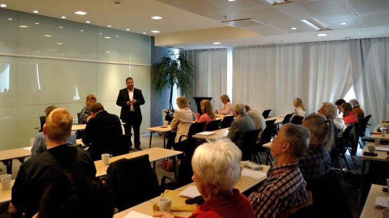 Lyssnande mötesdeltagare sitter med ryggen mot kameran vid smala bord i ett konferensrum.