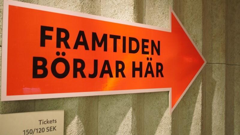 En orange skylt i form av en pil med texten FRAMTIDEN BÖRJAR HÄR i svart.