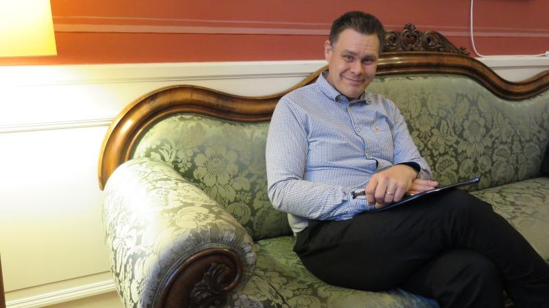 Medelålders man med kort mörkt hår klädd i ljusblå skjorta och mörka byxor. Händerna vilar i knät och han småler, tillbakalutad i en soffa.