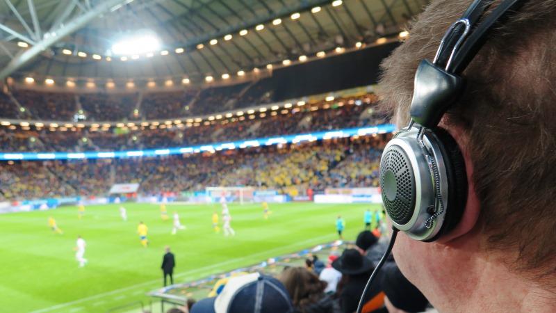 Friends arena. Ett bortvänt huvud med hörlurar till syntolkningsutrusning i förgrunden, pågående fotbollsmatch i oskärpa i bakgrunden.