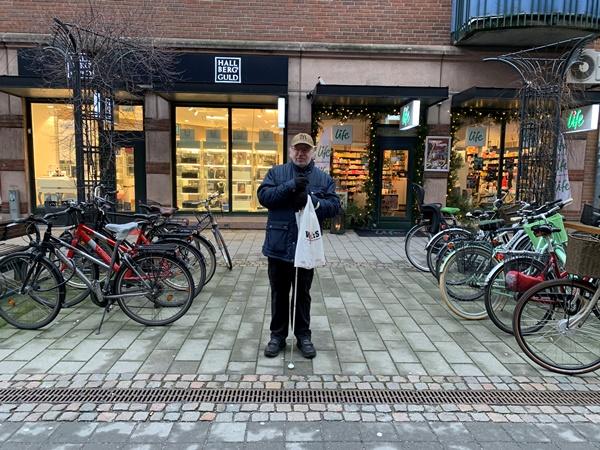 Man med grått helskägg och vit käpp står på stenbelagd affärsgata mellan två cykelställ.