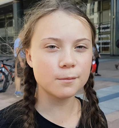 Närbild på flicka med brunt hår i långa flätor och bestämd uppsyn.