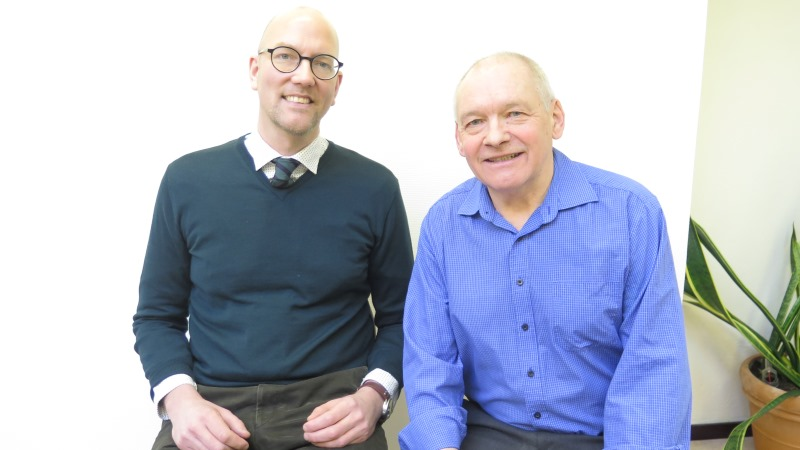 Gustav Hemming är skallig, har runda glasögon och bär skjorta och slips under v-ringad tröja. Kent Ivarsson har kal hjässa, vitt, kort hår på sidorna och bär klarblå skjorta. Båda ler brett.