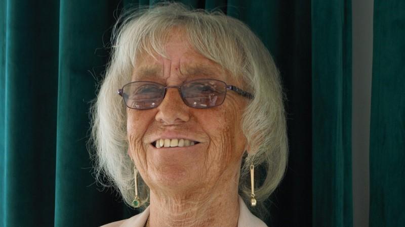 En leende kvinna i glasögon och ljusrosa dress. Pagefrisyr i grått hår och hängande örhängen i guld med en grön sten i.