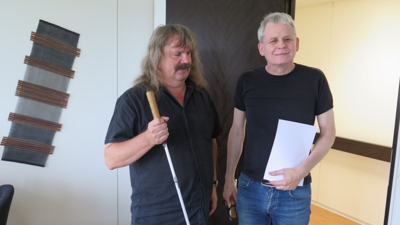 Håkan Thomson har axellångt hår och mustasch och håller i en vit käpp, Lennart Karlsson har kort, grått hår och håller i ett papper på punkt i ena handen och en ihopvikt käpp i den andra. De står i dörröppningen till en korridor.