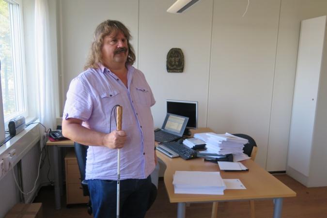 Håkan Thomsson, SRF.s ordförande, framför sitt skrivbord med dator och högar med punktskrift