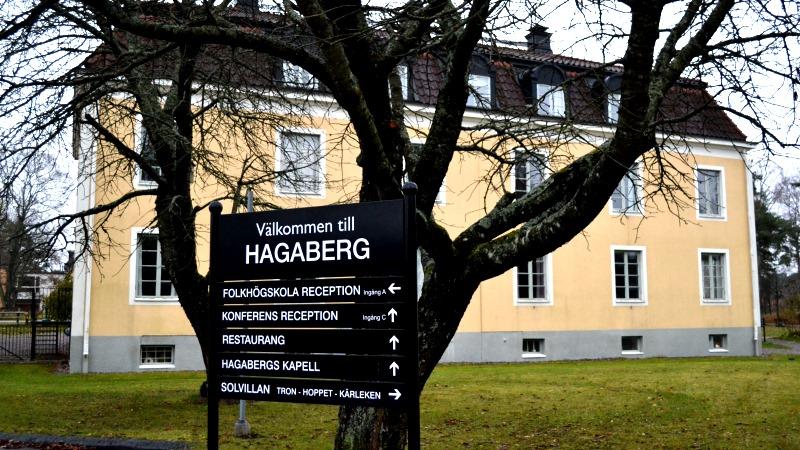 Stort gult hus i puts, en skola, ligger i en park. I förgrunden ett avlövat träd och en stor skylt för Hagabergs folkhögskola.