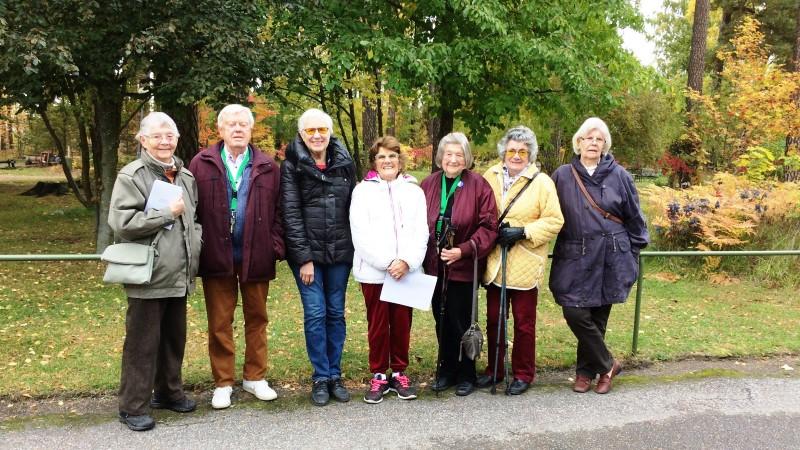 En grupp seniorer står tillsammans på rad framför en park med lummiga träd. Sju personer varav en man.