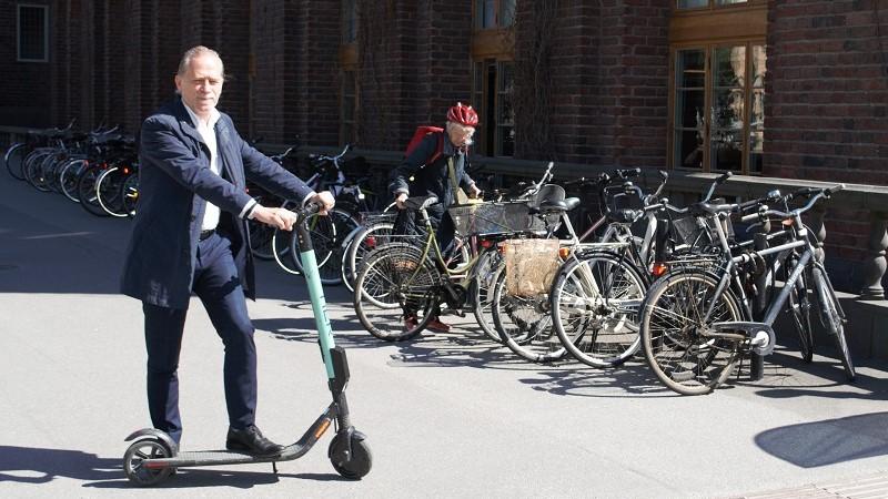 Daniel Helldén, en vithårig man i blå kostym utan slips står med ena foten på en elsparkcykel som han är på väg att parkera.