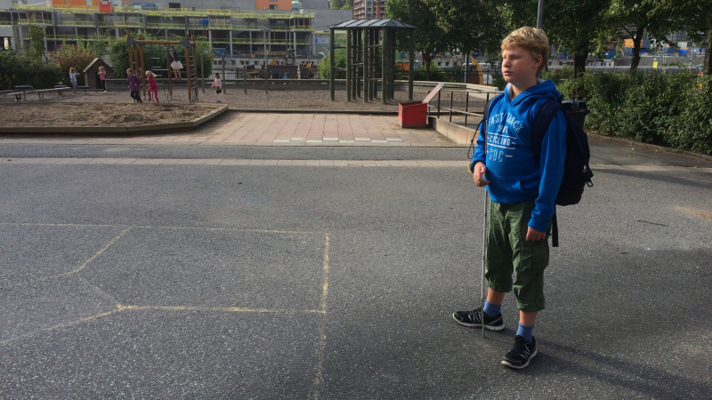 En pojke står med vit käpp och ryggsäck på en skolgård.