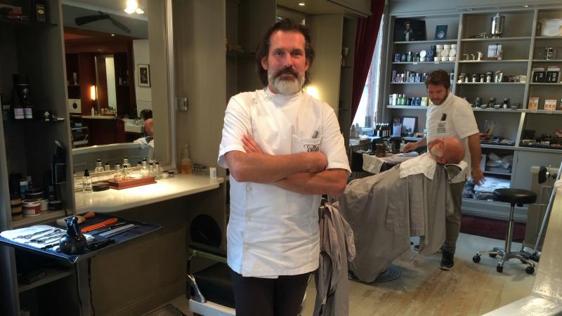 Håkan Ström har långt, gråspräckligt skägg och en vit barberarskjorta.