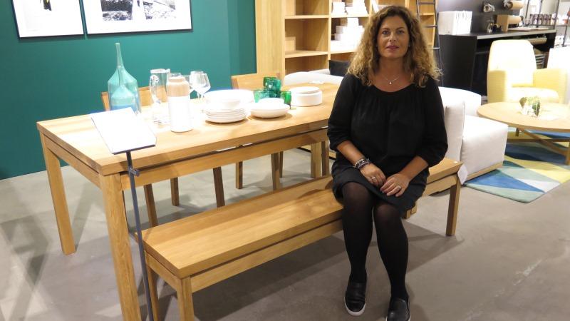 Madeleine Mortensen sitter vid en matgrupp av ljust trä med en grön fondvägg bakom sig.