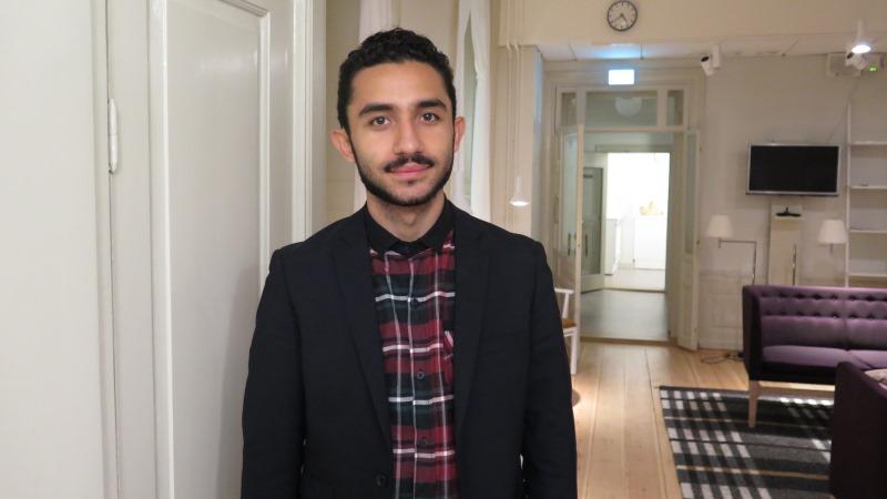 Daniel Riazat har en rutig skjorta och svart kavaj.