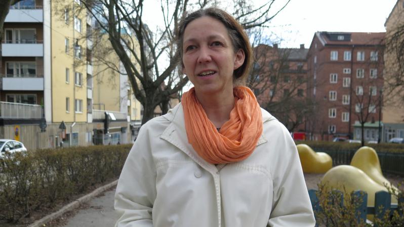 En kvinna med mörkt hår, ljus jacka och orange halsduk.