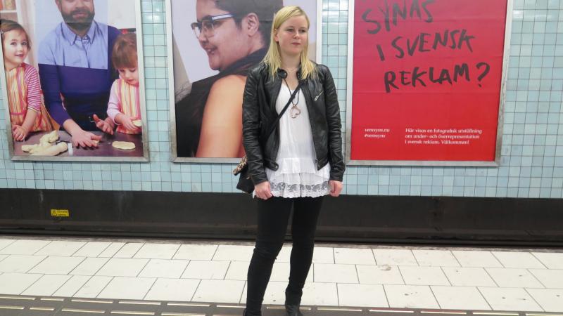 En kvinna som står på en tunnelbaneperrong med utställningen bakom sig.