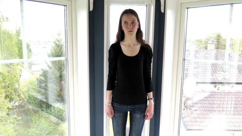 Louise Jannering står vid fönster i tornet som tillhör hennes hus. Hon har mörkt hår och en svart tröja.