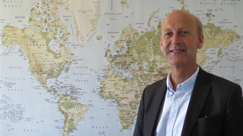 Anders Boman står framför en världskarta. Han har kavaj, skjorta och tunnt hår.