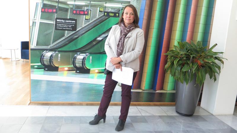 En kvinna i kostym står framför en tapet där man ser en bit av Stockholms tunnelbana.