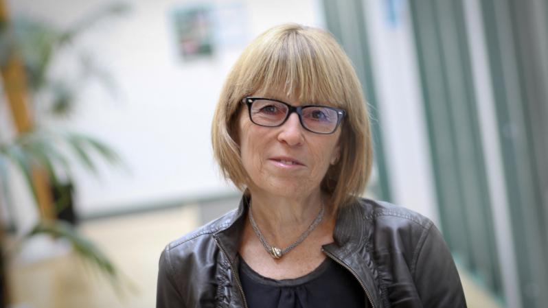 En kvinna med blond page och brun skinnjacka.